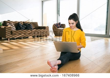 Beautiful young woman at home sitting on the floor, working on laptop, writing something