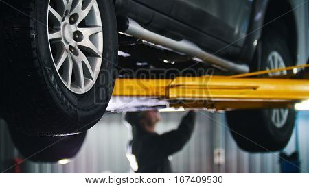 Car lifted in automobile service for fixing, worker repairs detail, telephoto