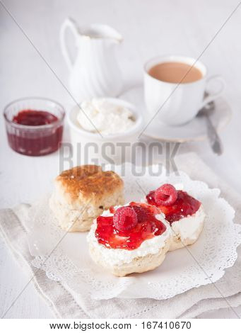 Traditional English cream teas, scones with strawberry jam and raspberries with tea on the white table, selective focus