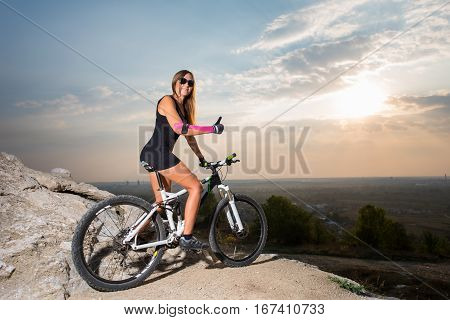 Woman With The Mountain Bike Under A Sky At Sunset