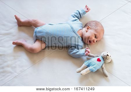 Cute newborn baby boy in blue striped onesie lying on bed, teddy bear toy with red heart next to him