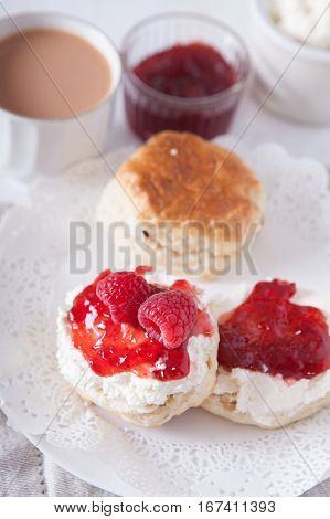 Scones with strawberry jam and raspberries with tea on the white table, selective focus