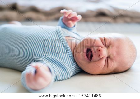 Cute newborn baby boy in blue striped onesie lying on bed, crying. Close up.