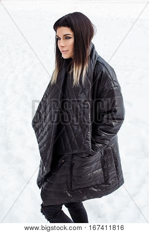 Cocky model close-up in snow looking aside. She is wearing black baggy jacket