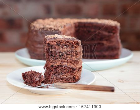 Piece of chocolate cake with frosting, cut cake on the back