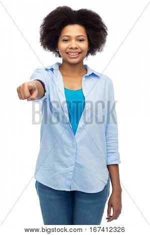 people, race, ethnicity, gesture and choice concept - happy african american young woman pointing finger to you over white