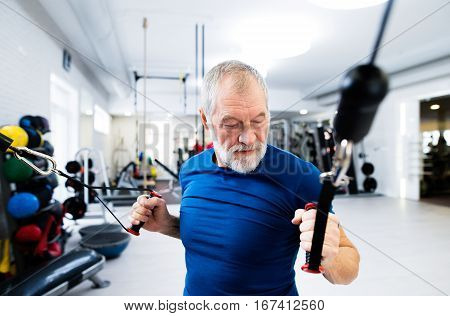 Fit senior man in sports clothing in gym working out with resistance bands.