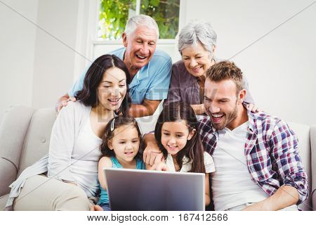 Smiling multi generation family using laptop at home