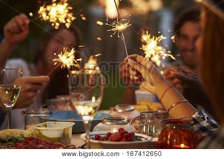 Friends With Sparklers Eating Food And Enjoying Party
