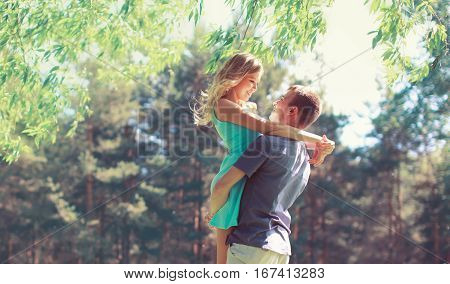 Happy Young Couple In Love Hugging Enjoys Spring Day, Loving Man Holding On Hands His Woman Carefree