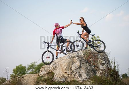 Couple Standing With Bicycles On The Rock Under Evening Sky