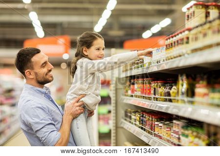 family, sale, shopping, consumerism and people concept - happy father with child buying food at grocery store