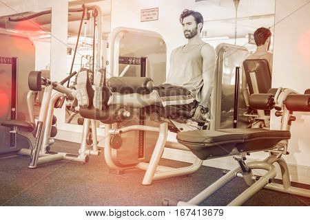 Focused man using weights machine for legs at gym