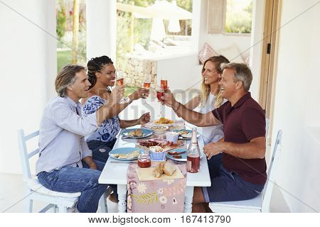 Two couples at a dinner table on a patio raise their glasses