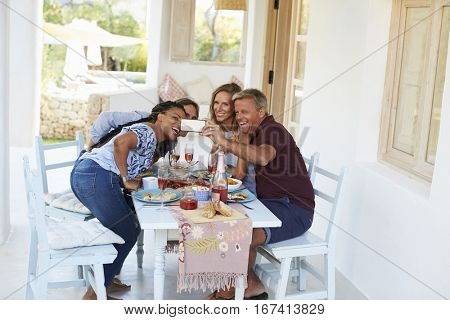 Two couples at dinner on a patio leaning in for a selfie