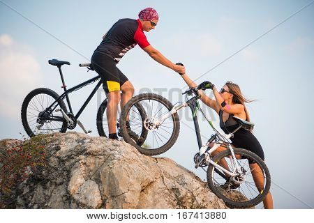 Bicyclist Helping To His Partner With A Mountain Bike