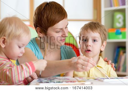 Children boys with teacher painting in playschool
