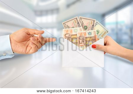 Woman bribing a man with an envelope full of money in an office building suggesting a corrupt system