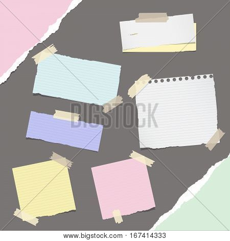 Pieces of different size ruled colorful note, notebook, copybook paper sheets stuck with sticky tape on dark gray background.