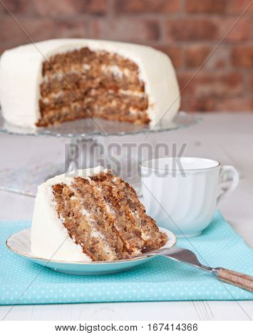 Piece of cut hummingbird cake with the cake on the stand, selective focus
