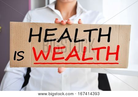Health is wealth saying written on a cardboard sign held by a woman