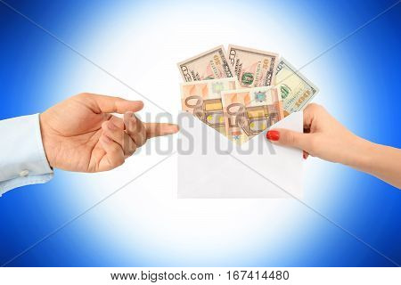 Woman bribing a man with an envelope full of money