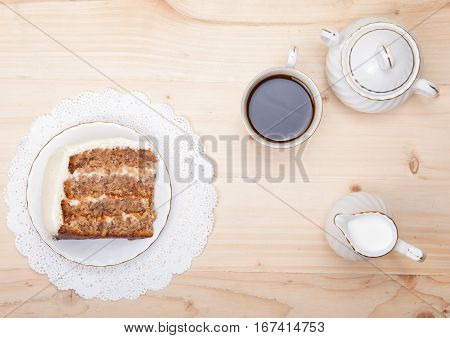 Top view of hummingbird cake with white frosting, with coffee and milk on the wooden table