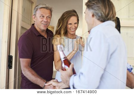 Couple greeting their guests at the door of their home