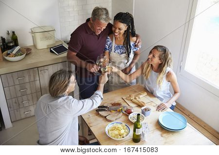 Two couples preparing dinner make a toast, elevated view