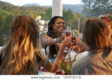 Couples toasting at dinner on a terrace, over shoulder view