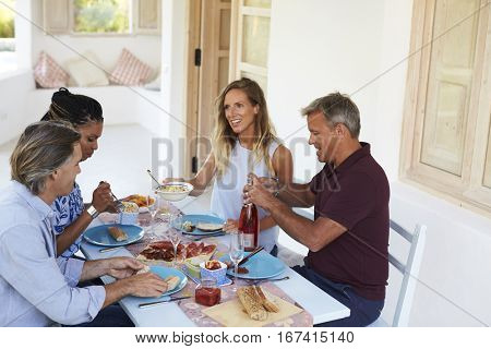 Two couples sitting down for dinner at a table on a patio