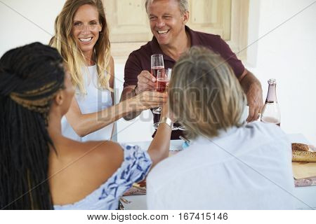 Two couples making a toast before dinner, close up