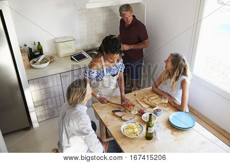 Two couples preparing food and drinking wine, elevated view