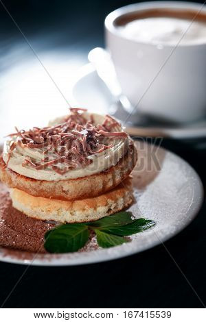 Cake on plate near cup of coffee on dark wooden table