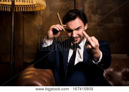 Rich man challenging whole of society, cheater, disrespect. Handsome man sitting on sofa and smoking cigar in restaurant or cafe.