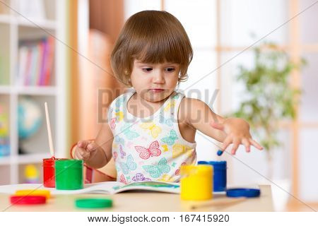child girl painting her fingers in bright colors
