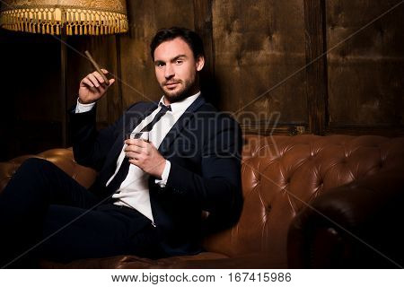 Wealth, business concept. Handsome man in business suit smoking cigar and drinking whiskey. Happy rich businessman in men's club spending free time.