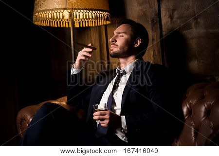 Handsome man drinking whiskey and smoking cigar. Billionaire man resting and relaxing while sitting on sofa in men's club. Luxury concept.
