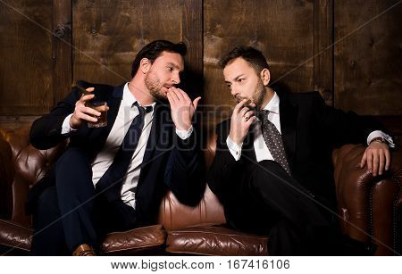 Collusion in business and global conspiracy between two successful businessmen. Rich men spending time in men's club and solving global problems.