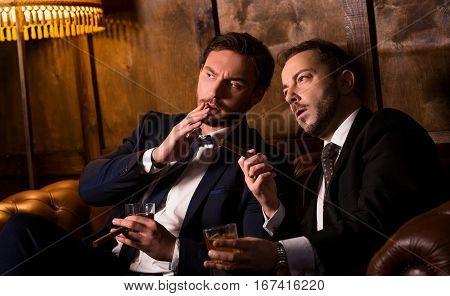 Rich men spending time in men's club and solving global problems. Collusion in business and global conspiracy between two successful businessmen.