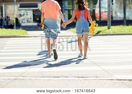 summer holidays, extreme sport, relations and people concept - happy teenage couple with short modern cruiser skateboards crossing city crosswalk