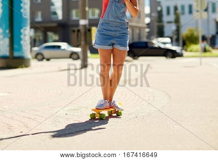 summer, extreme sport and people concept - teenage girl riding short modern cruiser skateboard on city street