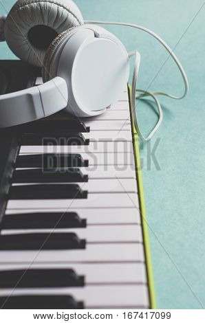 Synth and white headphone on green background