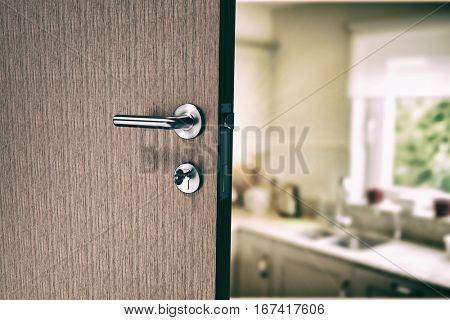 Closeup of door with doorknob and key against kitchen interior