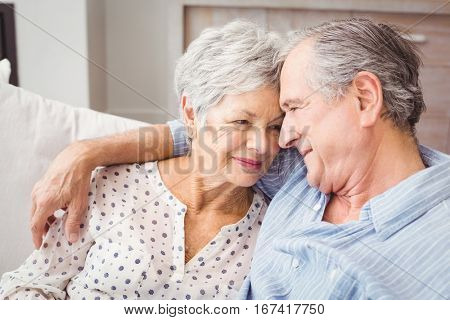 High angle view of romantic senior couple sitting on sofa at home