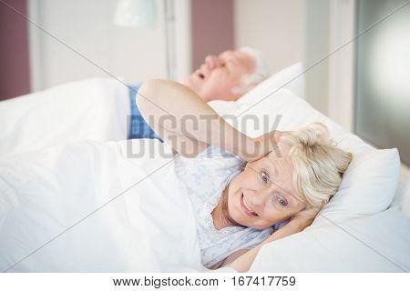 Irritated senior woman blocking ears while man snoring on bed