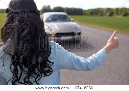 road trip, travel, gesture and people concept - woman hitchhiking and stopping car with thumbs up gesture at countryside