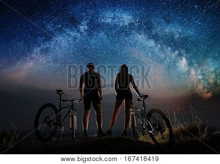 Couple Cyclists With Mountain Bikes At Night Under Starry Sky