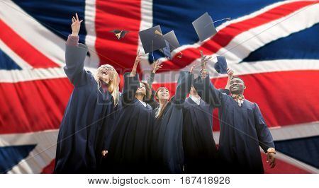 education, graduation and people concept - group of happy international students in bachelor gowns throwing mortarboards up over english flag background