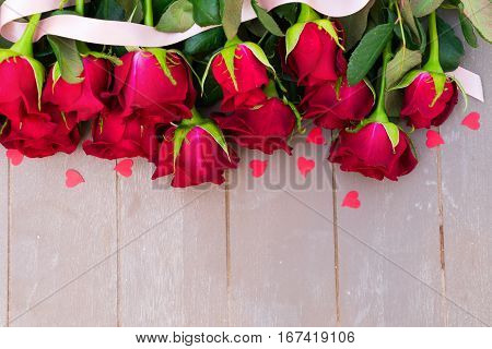 Dark Red buds of valentines day roses flowers border on wood with ribbon and hearts